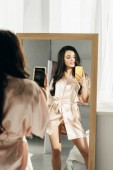 """Постер, картина, фотообои """"привлекательная женщина брюнетка принимая Фото стоя возле зеркала"""""""