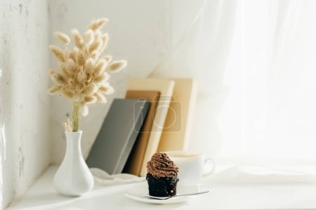 Photo for Willow catkins in vase near cupcake, cup of coffee and books - Royalty Free Image