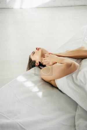 Photo pour Jolie fille allongée sur le lit et toucher le cou dans la chambre à coucher moderne - image libre de droit