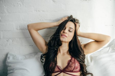 Photo for Cheerful and sexy brunette young woman in lingerie lying on bed and touching hair - Royalty Free Image