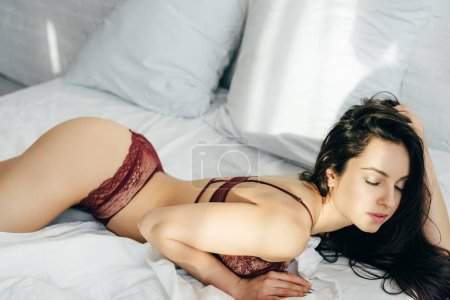 sexy young woman in lingerie with closed eyes lying in bedroom with sunlight