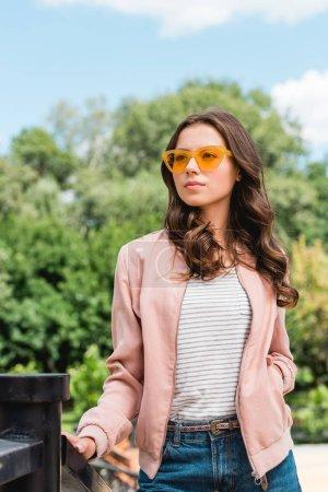 attraktives Mädchen mit Sonnenbrille steht mit der Hand in der Tasche im Park