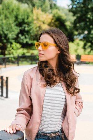 Photo pour Jolie fille en lunettes de soleil debout avec la main dans la poche dans le parc - image libre de droit