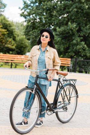 Photo pour Fille gaie dans les lunettes de soleil et chapeau debout avec vélo dans le parc - image libre de droit