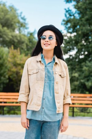 Photo pour Fille heureuse dans les lunettes de soleil et chapeau souriant tout en se tenant dans le parc - image libre de droit
