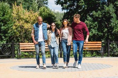 Foto de Feliz grupo multicultural de amigos sonriendo mientras caminaba en el Parque - Imagen libre de derechos