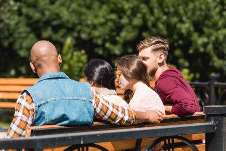 Photo pour Vue arrière de l'homme afro-américain assis avec des amis sur le banc - image libre de droit