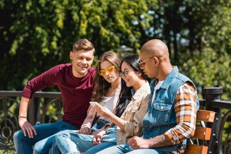 fröhliche multikulturelle Freunde, die auf Bank sitzen und aufs Smartphone schauen