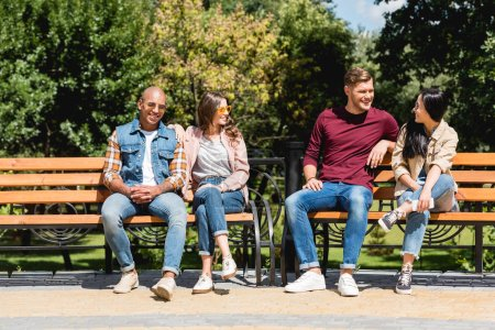 Photo for Cheerful multicultural friends smiling while sitting on benches in park - Royalty Free Image