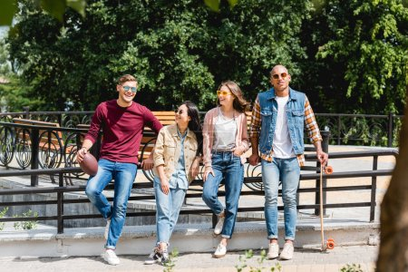 Photo for Cheerful multicultural young men standing with longboard and american football near attractive girls - Royalty Free Image