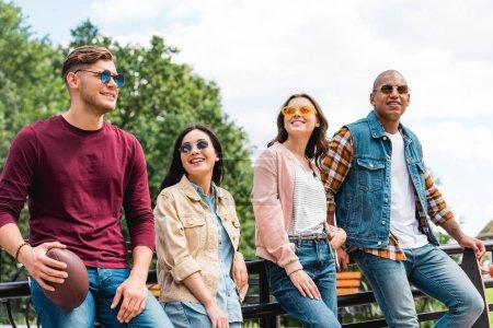 Photo pour Joyeux multiculturel jeunes hommes en lunettes de soleil permanent avec longboard et football américain près de jolies filles - image libre de droit