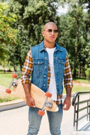 Photo pour Bel homme afro-américain en lunettes de soleil debout avec longboard - image libre de droit