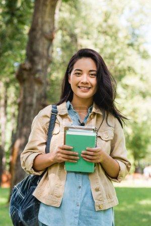 Photo pour Heureuse jeune femme tenant des livres et souriant dans le parc - image libre de droit