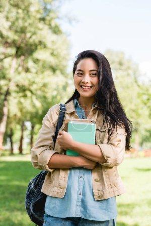 hübsche junge Frau hält Bücher in der Hand und lächelt im Park
