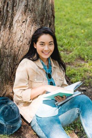 Photo pour Jolie étudiante souriante tout en étant assis dans le parc avec des livres - image libre de droit
