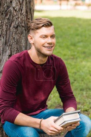 alegre estudiante sosteniendo libros y sonriendo en el parque