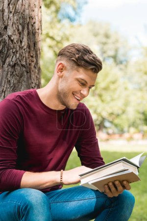 Photo for Cheerful student reading book and smiling while sitting in park - Royalty Free Image