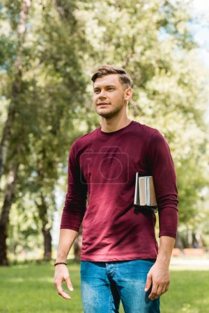 Photo for Handsome student standing with books and smiling in park - Royalty Free Image