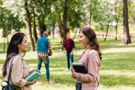 selective focus of cheerful girls talking while standing with books near students playing american football