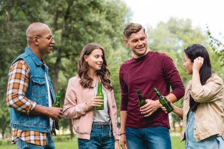 Photo for Happy multicultural friends holding bottles with beer while standing in park - Royalty Free Image