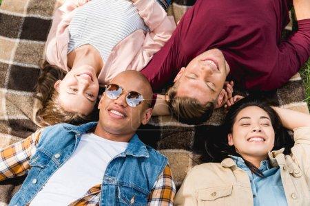 Foto de Vista aérea de alegres amigos multiculturales en manta a cuadros - Imagen libre de derechos
