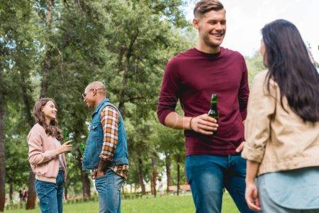 Foto de Felizes amigos multiculturales hablar mientras mantiene botellas con cerveza en el Parque - Imagen libre de derechos