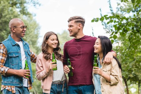 Photo for Cheerful multicultural group of friends holding bottles with beer and talking in park - Royalty Free Image