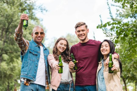 happy multiethnic group of friends holding bottles with beer and looking at camera