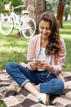 cheerful girl looking at smartphone while sitting on checkered blanket in park