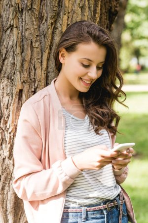 chica alegre mirando el teléfono inteligente mientras está de pie cerca del árbol en el parque