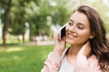 Photo for Attractive girl talking on smartphone and smiling in park - Royalty Free Image