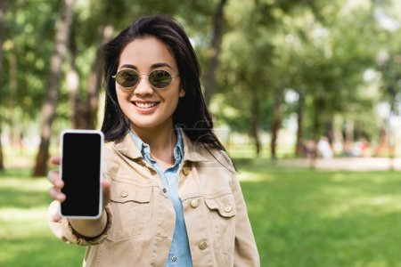 Photo for Selective focus of cheerful girl in sunglasses holding smartphone with blank screen - Royalty Free Image