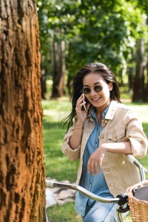Photo for Smiling young woman in sunglasses talking on smartphone near bike in park - Royalty Free Image