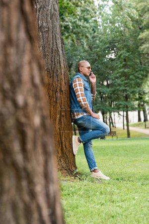 Photo pour Foyer sélectif de bel homme afro-américain parlant sur smartphone tout en se tenant dans le parc - image libre de droit