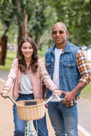 Photo pour Heureux homme afro-américain debout près de vélo joyeuse petite amie - image libre de droit