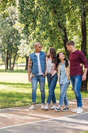 Photo pour Heureux multiethnique amis câlins tout en marchant ensemble dans le parc - image libre de droit