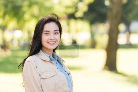 Photo for Cheerful young woman smiling while looking at camera in park - Royalty Free Image