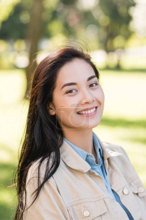 Photo for Attractive young woman smiling while looking at camera in park - Royalty Free Image