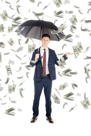 Photo pour Homme d'affaires souriant en costume avec parapluie geste sous la pluie de l'argent - image libre de droit