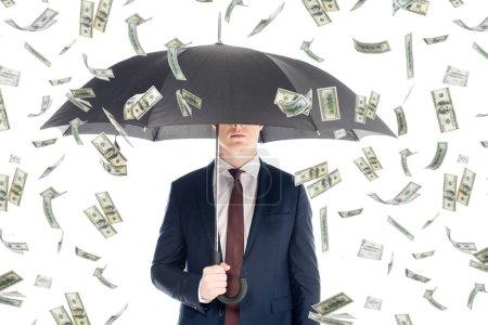 Foto de Hombre de negocios en traje con la cara oscura y paraguas bajo la lluvia de dinero - Imagen libre de derechos