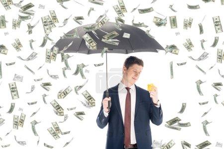 Foto de Hombre de negocios acertado en traje con paraguas y hucha amarillo bajo lluvia de dinero sobre fondo blanco - Imagen libre de derechos