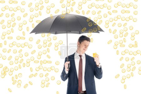 Photo for Successful businessman in suit holding umbrella and yellow piggy bank under coins rain on white background - Royalty Free Image