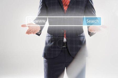 Foto de Recorta la vista del hombre de negocios en traje apuntando con las manos en la ilustración de barra de búsqueda en el frente - Imagen libre de derechos