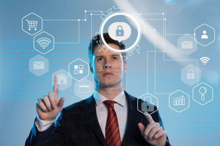 Photo for Handsome businessman in suit pointing with fingers at cyber security icons in front on blue background - Royalty Free Image