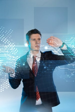 Photo for Handsome businessman in suit pointing at network illustration in front on blue background - Royalty Free Image