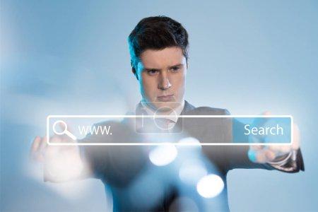 Photo pour Homme d'affaires confiant en costume pointant à l'illustration de barre de recherche en face sur fond bleu - image libre de droit