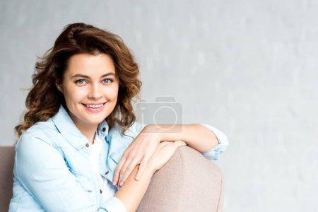 Foto de Hermosa rizada mujer en camisa sentada en el sofá con sonrisa en gris - Imagen libre de derechos