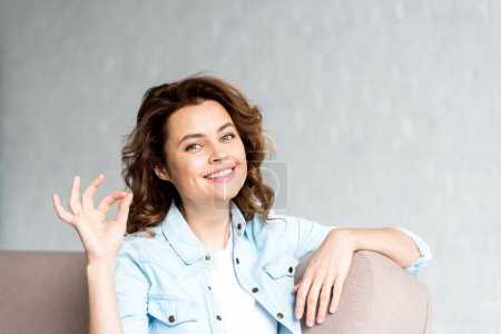 Photo for Happy curly woman in shirt sitting on sofa and showing okay sign on grey - Royalty Free Image