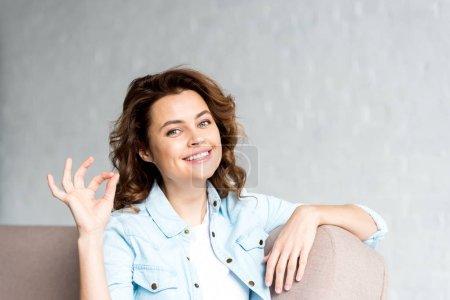 Foto de Feliz rizada mujer en camisa sentada en el sofá y que muestra bien en gris - Imagen libre de derechos