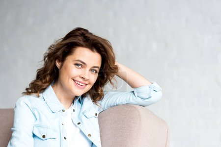 Joyful curly woman in shirt sitting on sofa and looking at camera with smile on grey
